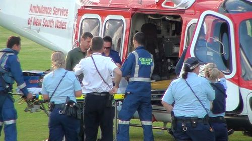 A two-year-old girl is loaded into the Ambulance Helicopter at Hazlett Oval, Macquarie Fields, after a near-drowning incident at Long Point. (9NEWS)
