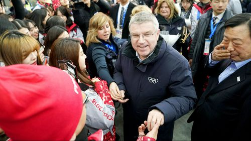 IOC President Thomas Bach is welcomed by volunteer workers in Pyeongchang. There are rising tensions between North and South Korea amid planned unity events. (AAP)