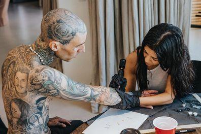 Kourtney Kardashian gives Travis Barker a tattoo.