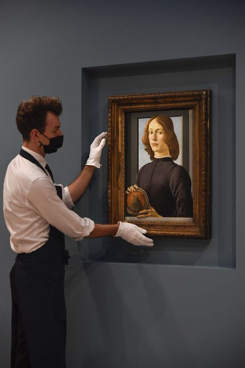 A member of the staff wearing a face mask to curb the spread of COVID-19 holds the painting 'Young Man Holding a Roundel' by the Italian Renaissance painter Sandro Botticelli at Sotheby's, in London, Wednesday, Dec. 2, 2020.