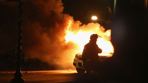 A squad car burns after protestors rioted following the grand jury announcement in the Michael Brown case. (Getty Images)
