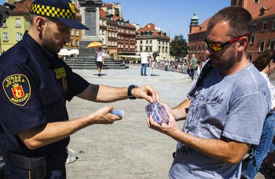 A city guard gives water to citizens during the heat wave in Warsaw, Poland.