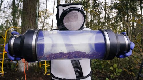 Sven Spichiger, Washington state Department of Agriculture managing entomologist, displays a canister of Asian giant hornets vacuumed from a nest in a tree behind him in Blaine, Wash.