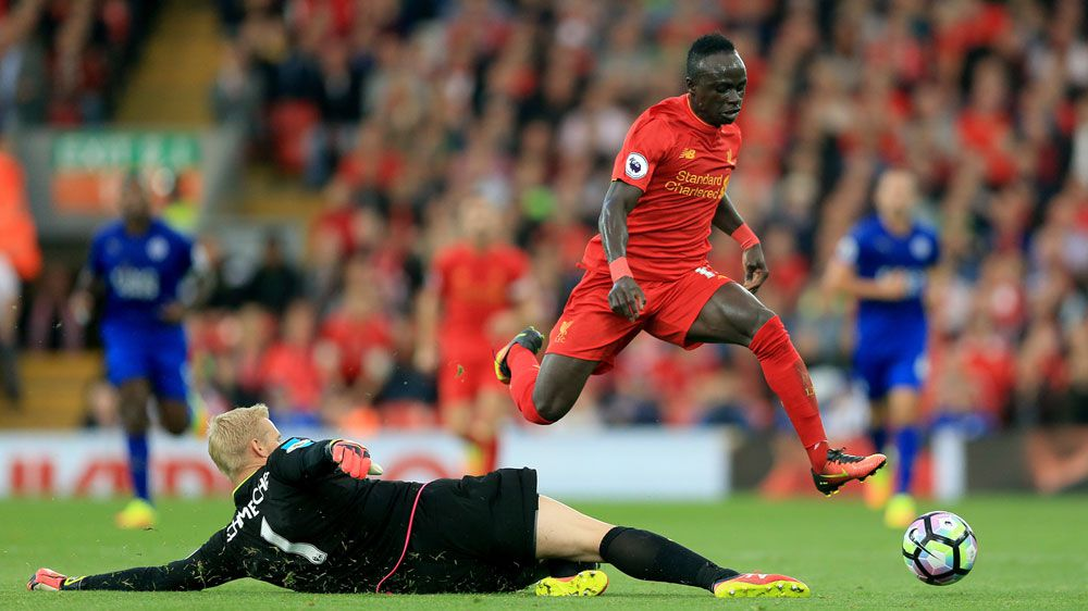 Liverpool's Sadio Mane hurdles Kasper Schmeichel (AAP)