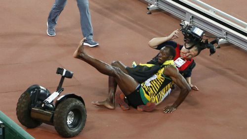 Usain Bolt and a cameraman fall to the found at the Bird's Nest in Beijing.