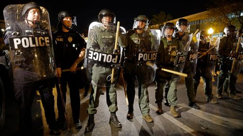 Police stand in formation as a curfew approaches in Baltimore, on April 29, 2015. (AAP)