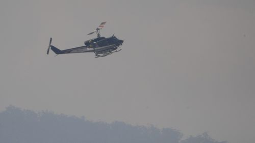 A Tasmanian Fire Service helicopter pictured on patrol, at Huonville, near Hobart yesterday.