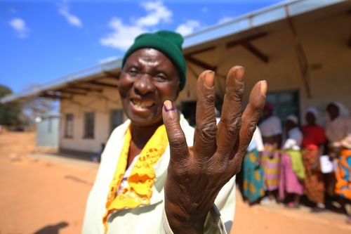 An elderly woman shows her little finger being marked with an ink marker after she casted her vote at the Batsirai Primary school just outside Harare, Zimbabwe, 30 July 2018.