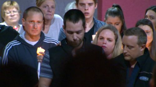 Mourners held candles at the Carrum Downs shopping centre car park.