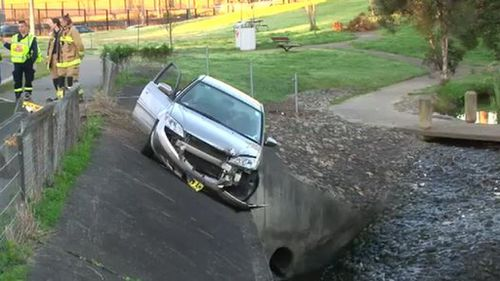 Woman rescued from car hanging over storm water drain in Sydney