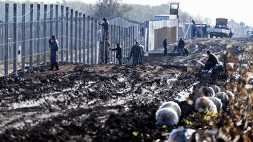 Prisoners build a new, second fence at the Hungarian-Serbian border near Gara village on October 27, 2016 as part of its efforts to keep migrants and refugees from freely entering the country. The new fence will have an electronic surveillance equipment.