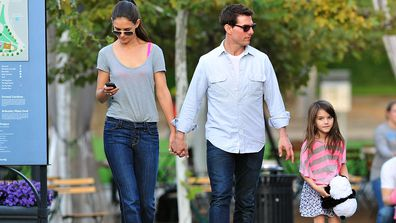 Tom Cruise, Katie Holmes and Suri Cruise walk together on October 8, 2011.