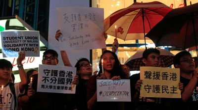 Malaysian activists hold placards and umbrellas during a rally to support pro-democracy protests taking place in Hong Kong.