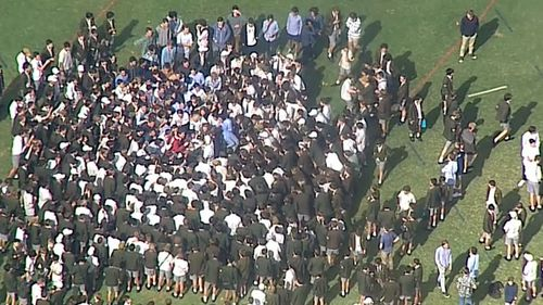 Students gather on the lawn of Trinity Grammar in Melbourne. (9NEWS)