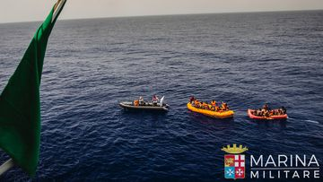 Rescuers tow migrants to the Italian Navy ship Vega, after the boat they were aboard sunk. (AAP)