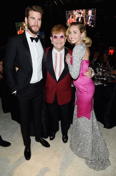 Liam Hemsworth, Elton John and Miley Cyrus in Moschino at Elton John's 2018 Oscars Viewing Bash in honour of the Elton John AIDS Foundation