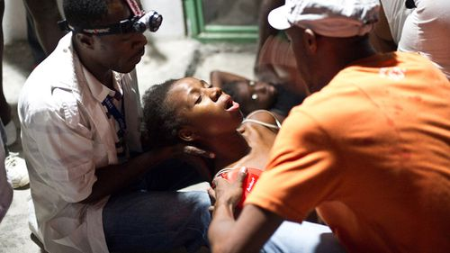 A woman faints in the arms of a medic in an emergency clinic in Port-au-Prince, Haiti on January 12, 2010 after a 7.0 earthquake rocked across the island nation. (Getty)