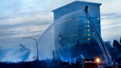 Firefighters spray water on the remnants of a structure fire in downtown LA. (AAP)