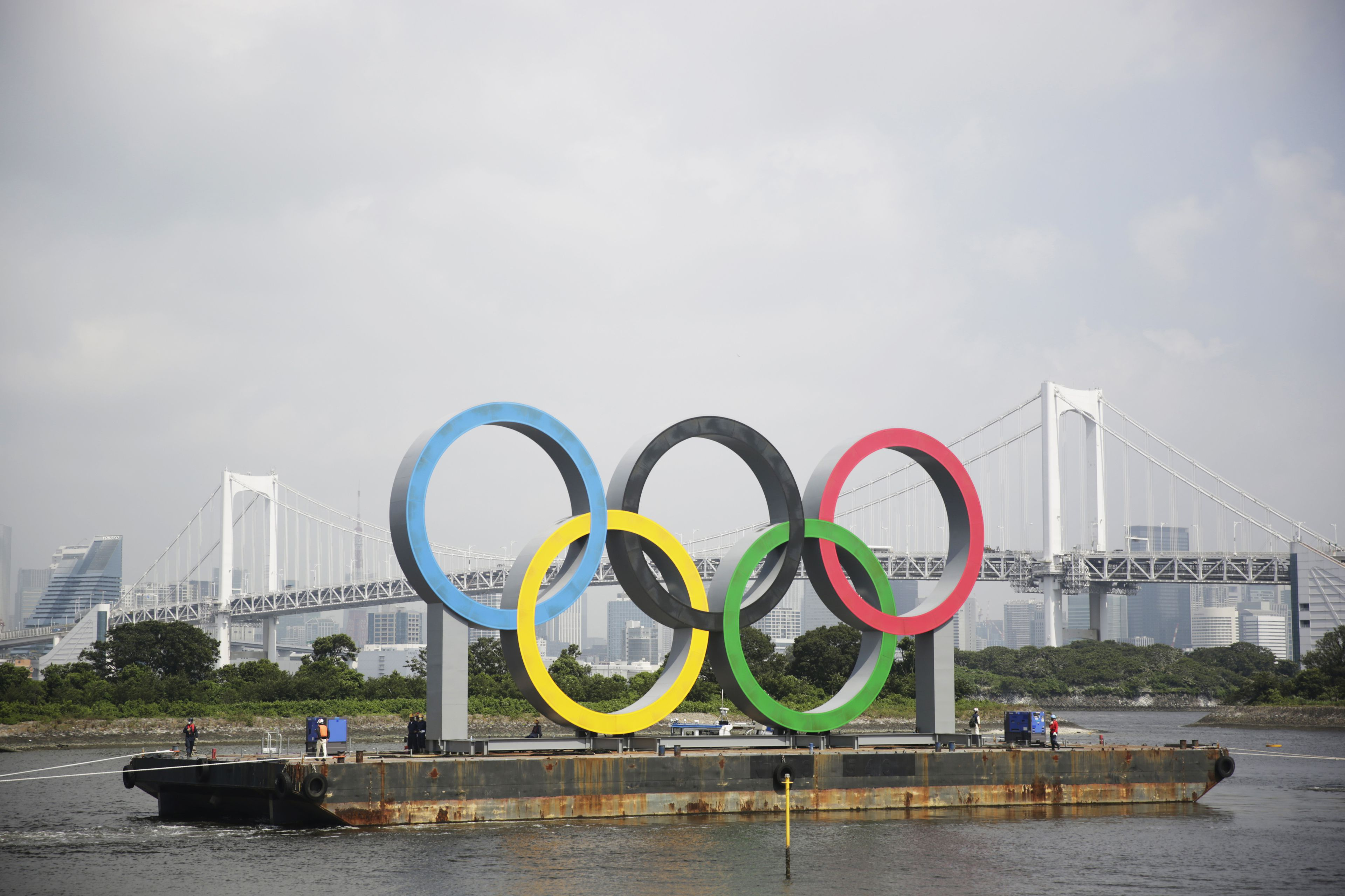 Tugboats move a symbol installed for the Olympic and Paralympic Games in Tokyo.