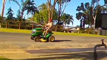Shirtless man takes off on ride-on mower during test drive