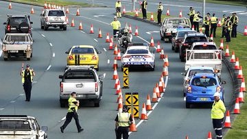 Motorists are stopped at a checkpoint on the Gold Coast Highway at Coolangatta on the Queensland/NSW border, on March 26