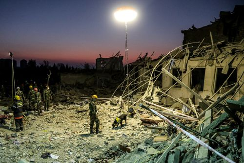 Search and rescue teams in Ganja, Azerbaijan, work at the blast site hit by a rocket during the fighting over the breakaway region of Nagorno-Karabakh on October 17