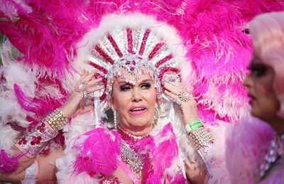 A drag queen adjusts her brilliant pink headdress. (AAP)