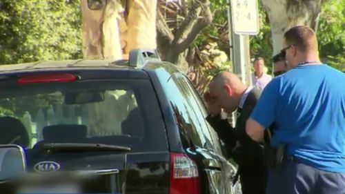 Police peer into the Kia yesterday afternoon after the boy was rushed to hospital. (9NEWS)