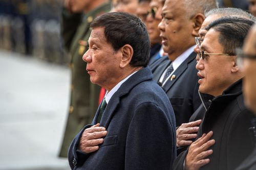 Philippine President Rodrigo Duterte, center, attends a wreath laying ceremony at the Tomb of the Unknown Soldier in Moscow, Russia, Friday, Oct. 4, 2019. (Yury Kadobnov/Pool Photo via AP)