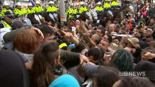 Police were caught in the middle of the angry protests by the two groups. (9NEWS)