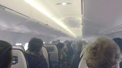 Passengers evacuate smoke-filled plane