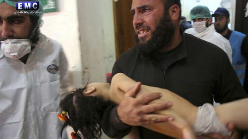 A man carries a child injured in the attack. (Edlib Media Centre via AAP)