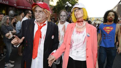 Husband and wife Dave Hester and Donna Hester, dressed as zombie Donald Trump and zombie Hillary Clinton, walk down Fifth Avenue