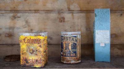 Old tins sit on a shelf inside the hut.