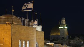 An Israeli flag flying with a minaret of a mosque and the Dome of the Rock in the background in Jerusalem's Old City.