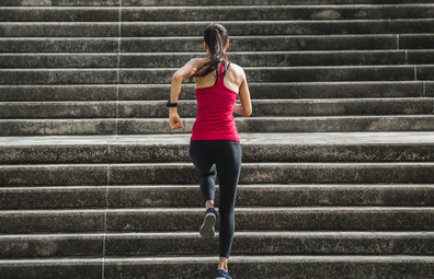 Woman exercising, running up a flight of stairs