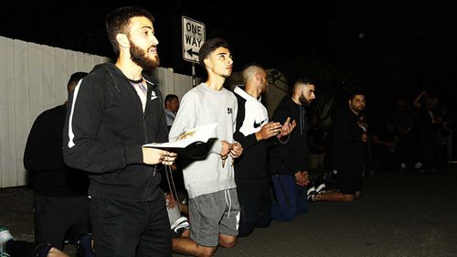 Protesters of a lurid mural in Newtown pray together. (AAP)