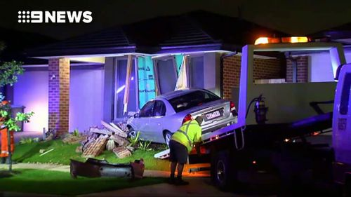 Workers attempt to remove the car. (9NEWS)