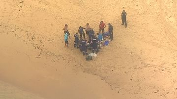 Lifeguards and emergency services performed CPR on the man found lying face down in the water near the centre of the beach