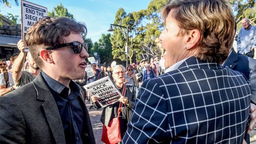 A protester confronts Christine Forster at an event for her brother, former prime minister Tony Abbott. (AAP)