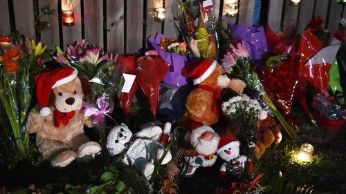Tributes have been laid in the street where the bodies of the children were found.