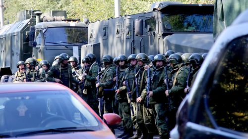 Military forces block the road to the site of attack at a vocational school in Kerch in Crimea, Russia.
