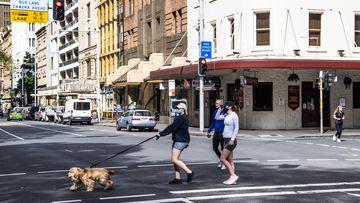 People walking a dog in Sydney CBD.