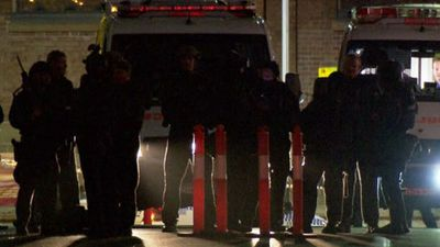 Members of the NSW Police Special Operations Group congregate after the raid. (9NEWS)