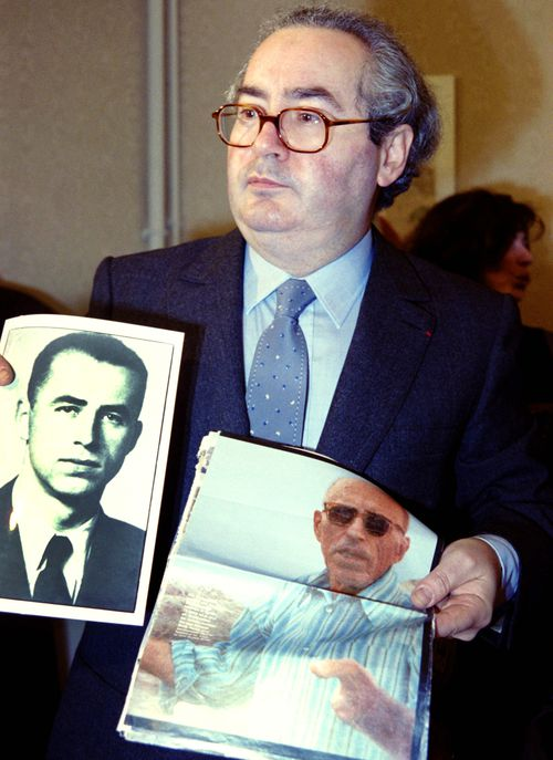 Nazi hunter Serge Klarsfeld displays two photos of WWII criminal Alois Brunner at a press conference in Paris on January 11, 1989. (Getty Images)