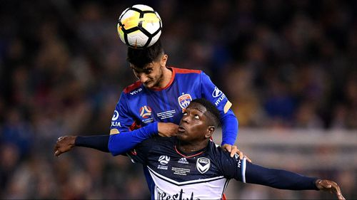 Johnny Koutroumbis of the Jets competes to head the ball with Leroy George of Victory. (AAP)