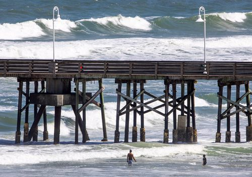 Beachgoers play in high surf next to the Main Street Pier in Daytona Beach, Florida. Hurricane Dorian, a powerful Category 5 storm, is expected to pass over The Bahamas before heading to the east of Florida on the upcoming week.