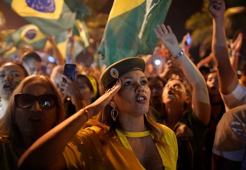 A supporter of Jair Bolsonaro celebrates his victory with a military style salute in Rio de Janeiro.