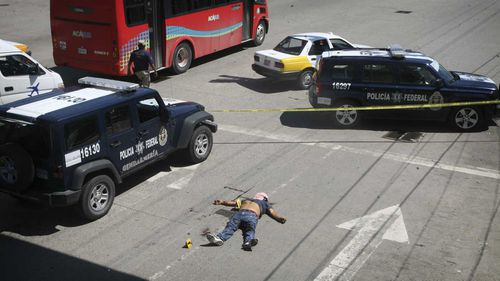A body lies in the middle of a busy street in Acapulco, Mexico. (AAP)