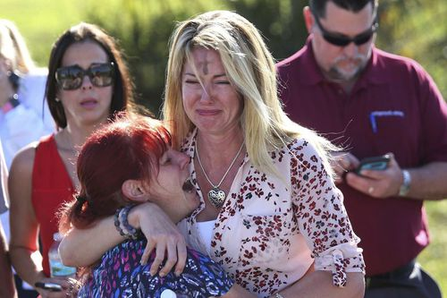 Two women cry as an active shooter mows down students at a Florida school.
